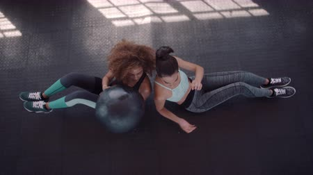 Top view of two young women training with medicine ball in gym. Females sitting back to back passing medicine ball to each other at fitness club.