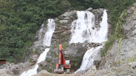 ambiental : Beautiful waterfall threatened by a bulldozer in Ecuadorian Andes mountains