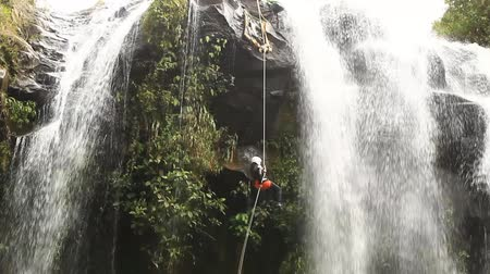 equipamentos esportivos : footage of a pesrson rappelling a waterfall.locked down, wide angle shot in Ecuadorian rainforest. Vídeos