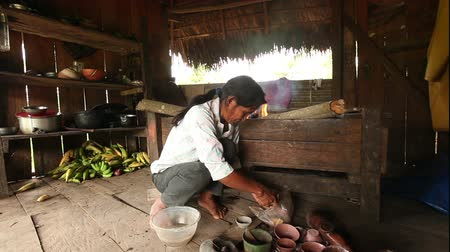 alkotás : Adult woman making pottery , rural scene in ecuadorian Amazonia, color preparation Stock mozgókép