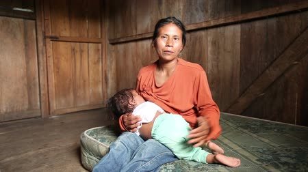 szoptatás : Mother with child living in very poor conditions,singing in quechua language,  Ecuadorian Amazonia Stock mozgókép