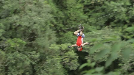 voz : Adult caucasian while zipline over tree canopy in a reversed position, camera pans to follow the subject