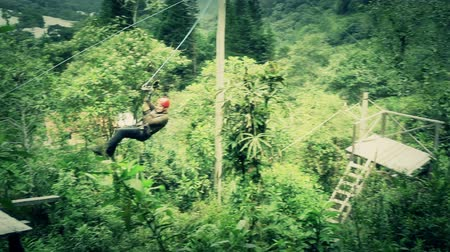 adrenalin : Zipline tour finish, color graded shot,camera pans RL