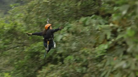 kable : Woman ridding a zip line, weaving shes arms like flying, camera pans RL to track the subject Wideo