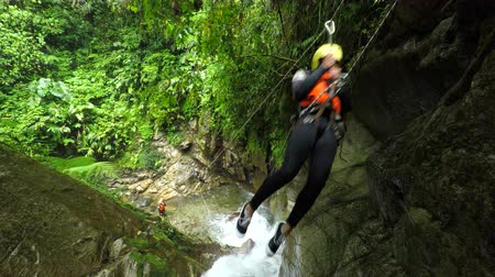 agua : Young tourist women on zip line in Ecuadorian canyoning experience, Llanganates national park, fixed camera, model released footage