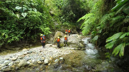 agua : Group of tourist, adults and kids on the Cashaurco canyon near Banos de Agua Santa, 4k pan left to right model released Stock Footage