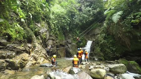 agua : Canyoning zip line in Ecuadorian rainforest, group of tourist descdent over waterfall
