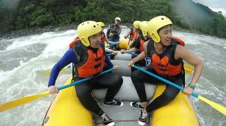 korejština : Group of eight asiatic people white water rafting back paddeling, on board camera with sound