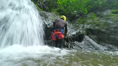 agua : Asiatic men tourist waterfall rappeling, slow motion