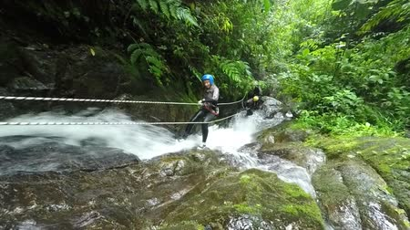 agua : Tourist descent a huge waterfall along with a canyoning instructor,hd footage , model released, static camera Stock Footage