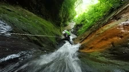 agua : Canyoning instructor rappeling close to impressive waterfall, includes audio