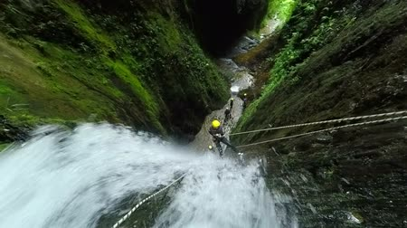 akció : Tourist descent a huge waterfall along with a canyoning instructor, 1080p footage , static camera includes audio