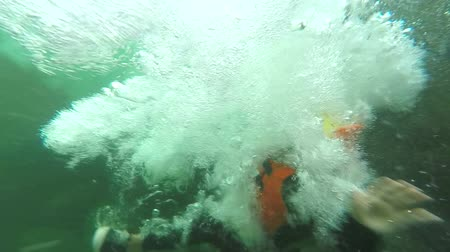 underwater video : young children plunging into waterfall, shot from the water level , camera tracks the subject underwater, slow motion 120fps Stock Footage