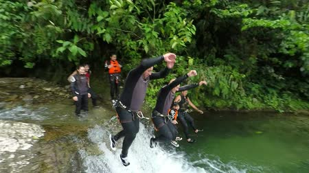 equador : Group of three adults and a kid jumping into a waterfall , slow motion