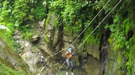 improvised : Young girl is sent by zip line over the waterfall while canyoning, action camera with sound