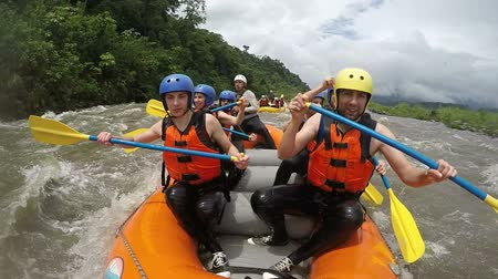 evezés : Team of seven people white water rafting. Onboard camera.