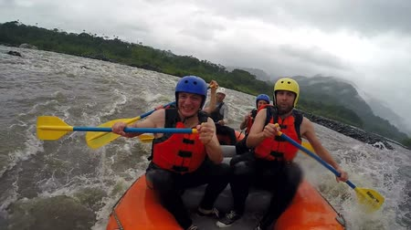kaland : Team of seven people white water rafting. Onboard camera.