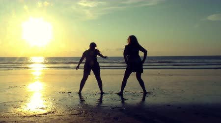 жир : Group of two plump girls jumps and taps their but against sunset slow motion