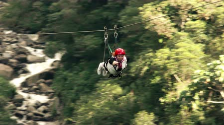 adrenalin : Woman on zipline ride superman style of riding tracking shot