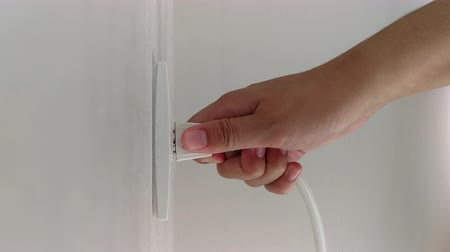 шнур : Close up of a hand plugging in a power cord Стоковые видеозаписи