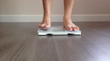 anorexia : human measuring weight on health scale close-up - human legs approaching to weighing digital instrument