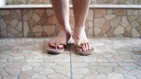 sandals : Male feet put on slippers Stock Footage