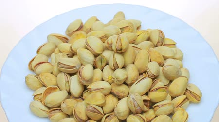 tuzlu : Lots of fried pistachios . On a white background.