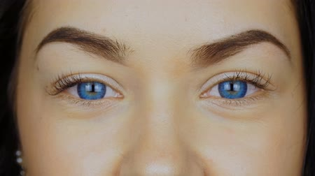 olhares : Close-up of a young womans eyes in blue contact lenses.
