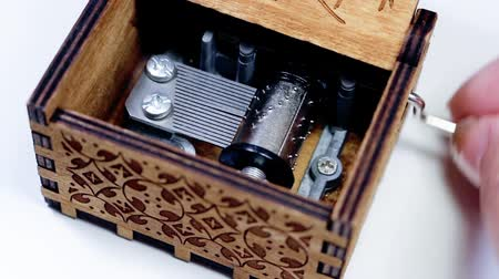notation : Womans hand opening and playing a music box. Macro of the music box mechanism and gears rotating as it plays.