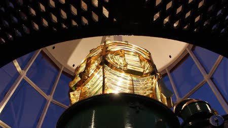 sinal : Close up of beautiful golden Fresnel lens inside Lighthouse, with gorgeous lights and shadows as lamp rotates. Stock Footage