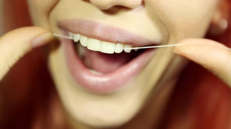 arcszín : Woman and teeth floss - Young caucasian woman flossing her teeth (close up woman smile)