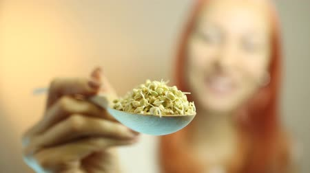 diety : Fresh Green Sprouts Buckwheat in the spoon Closeup. Young Beautiful Woman Eating Sprouts Buckwheat. Raw Healthy Organic Diet. Healthy Vegetarian Eco Food concept, Dieting