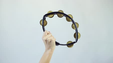 tambourine : Hands playing on tambourine (shaker), shake several times on white background