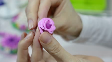 artistas : Artist makes jewelry from color Polymer Clay, artist at work. Workshop. Hobby - Art Clay Modeling. Tools for modeling. Handmade Production. Plasticine. Hands makes a pink rose Vídeos
