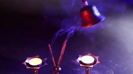 duch Święty : Sound vibrations - Buddhist Temple Bells. Hand holding bell on blue background with red light filter and incense. Asian spiritual traditions, ritual musical instruments. Puja. Mystical atmosphere
