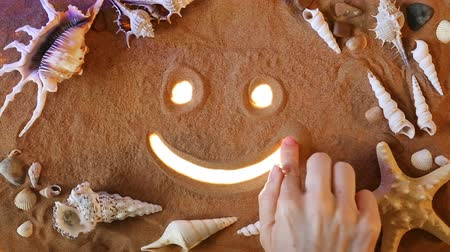 çizim : Hand drawing Smile Symbol in the Sand. Beach background. Top view. Positive concept: Smile (emoticon) icon is Highlighted by Rays of Light. Beautiful Sandy Background. Good Motivation Stok Video