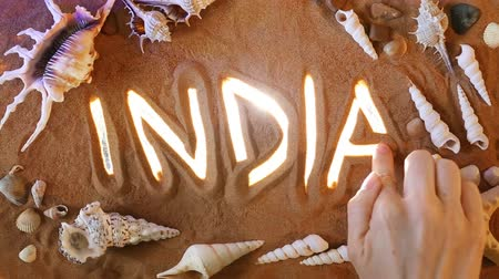 goa beach : Hand drawing India sign in the Sand. Travel. Top view. Spa concept: India sign icon is Highlighted by Rays of Light. Beautiful Romantic Sandy Beach Background. Sea Leisure