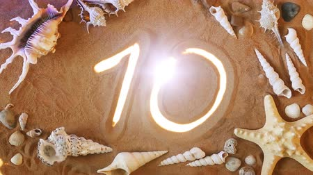 deset : Hand drawing Number Ten 10 Symbol in the Sand. Beach background. Top view. Number Ten 10 Symbol is Highlighted by Rays of Light. Beautiful Sandy Background. Hit parade count Dostupné videozáznamy