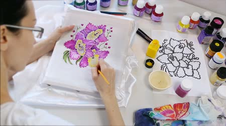 zanaat : Batik Process: Artist paints on Fabric, Batik-making. Painter Draws the Floral motif on a Silk white Cloth. Handmade Beautiful Art Design. Artist Workshop with Tools, Paints and Brushes for Batik. Stok Video