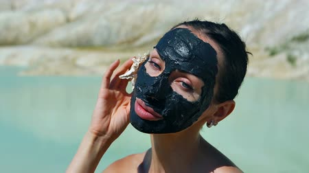 bahno : Woman with Black Clay Facial Mask. Beauty, Wellness. Spa Outdoor, Beautiful Young Woman with natural Dead Sea mud Facial Mask on her Face near the Lake with Black Cosmetic Healing Clay