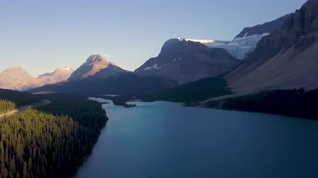 atmosféra : Aerial shot above lake next to road with mountains and forest while sunset in Rocky Mountains in Canada Dostupné videozáznamy