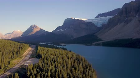 ledovec : Aerial shot above lake next to road with mountains and forest while sunset in Rocky Mountains in Canada Dostupné videozáznamy