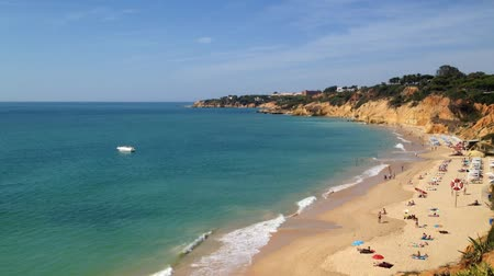 сценарий : MARIA LUISA, PORTUGAL - OCTOBER 04, 2014: Landscape view from the top of Maria Luisa beach in Albufeira, Algarve. People who are walking along the beach