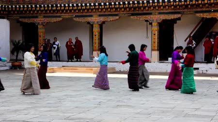 bhutan : at  drupchen festival, female dancers are appearing in the dzong of Punakha, Bhutan. They are wearing the traditional costume for their dance.