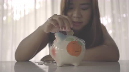 save : Woman inserts a coin into a piggy bank