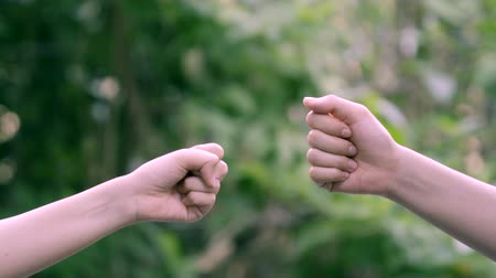 Couple play rock paper scissors hand game nature green background Stock mozgókép