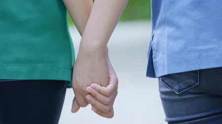two asian woman holding hands and moving foward Stock mozgókép