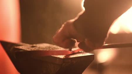 forging sword : The smith punches a hole in the blacksmiths mites Stock Footage