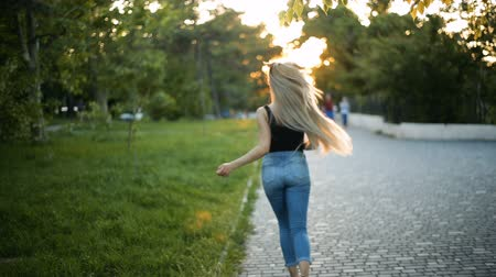extremo : Young sexy blond woman with very long flowing hair running in the park, toward the sunset. Back view. Moving off camera