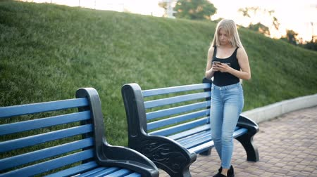 kostka : Young sexy blond woman with very long flowing hair walks in the park, looks into the smartphone, feels the discomfort of her feet, stops, sits down on a wooden bench.